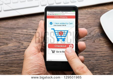 Close-up Of A Person's Hand Adding Items In Shopping Cart On Online Shopping App