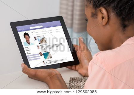 Close-up Of A Young Woman Using Social Networking Site On Digital Tablet