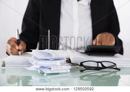 Close-up Of Businesswoman Calculating Tax With Eyeglasses And Paper Nail On Desk