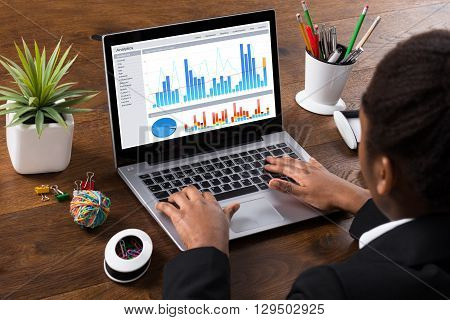 Young African Businesswoman Analyzing Graph On Laptop In Office