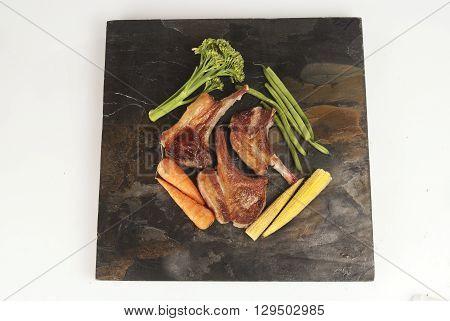 Freshly cooked pork chops against grey slate with vegetables