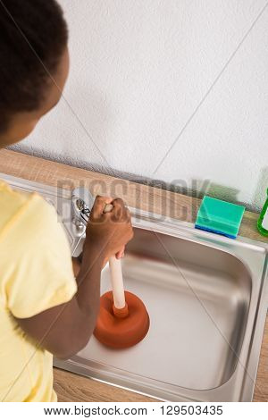 Young African Woman Using Plunger In Kitchen Sink