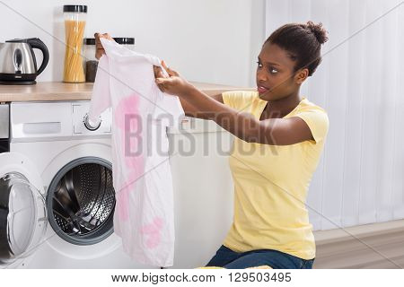Young African Woman Looking At Stained Cloth In Kitchen