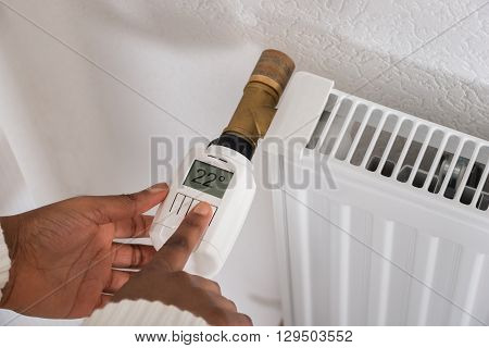 Close-up Of A Woman's Hand Adjusting Temperature On Thermostat