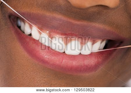 Close-up Of Young African Woman Flossing Teeth