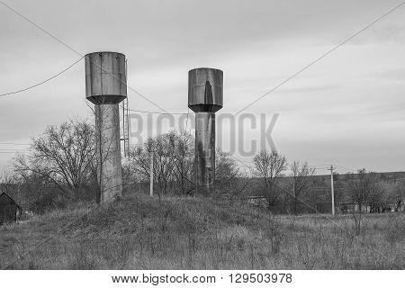 Round rusty metallic high towers on the vacant lot.