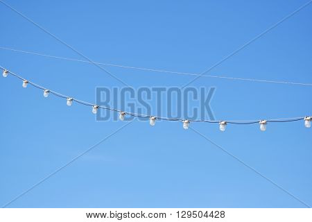 Light white bulbs hanging on electricity wire in clear blue sky background