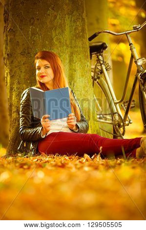 Nature outdoor concept. Beautiful girl is reading under the tree. Bike is behind woman. Lady is wearing red trousers leather jacket.