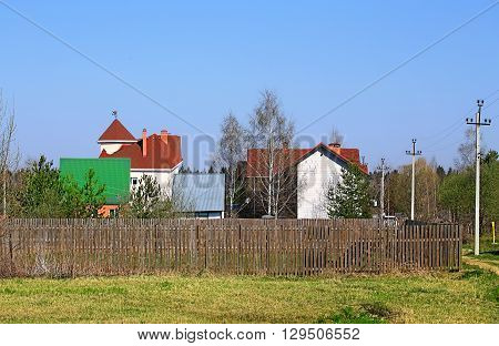 Cottages with colored roofs among the trees behind the fence