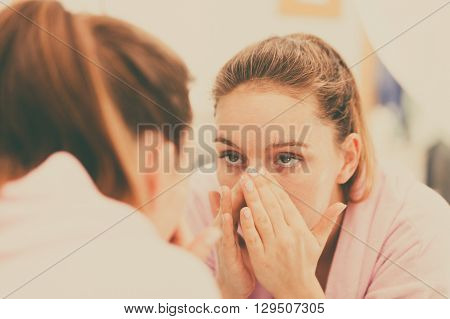 Woman cleaning peeling her face in bathroom making facial massage with scrub. Girl taking care of skin condition. Hygiene. Skincare spa treatment.