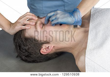 Physiotherapist doing a sinus massage therapy to male patient.