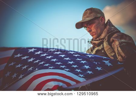 Young Army Veteran with American Flag Closeup Photo. Army Trooper with USA Flag.