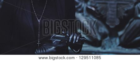 close-up of hands of girls in black leather gloves, grip the gun