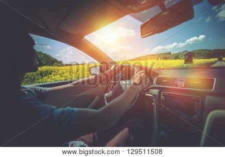 Summer Car Trip. Relaxed Men Driving Between Rapeseed Fields in Sunny Day. Car Driving.