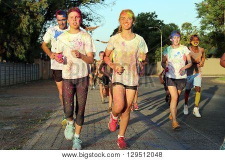 Rustenburg Marathon Club Rainbow Run - NOVEMBER 25: Running group of teens and man covered with powder paint at colour run on November 25 2015 Rustenburg South Africa.