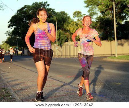 Rustenburg Marathon Club Rainbow Run - NOVEMBER 25: Two Chearful running teen girls covered with powder paint at colour run on November 25 2015 Rustenburg South Africa.