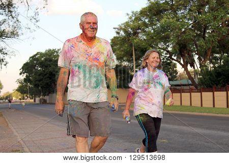 Rustenburg Marathon Club Rainbow Run - NOVEMBER 25: Old couple walking covered with powder paint at colour run on November 25 2015 Rustenburg South Africa.