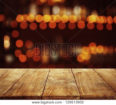 Empty wooden table and bokeh pub, bar of restaurant background.