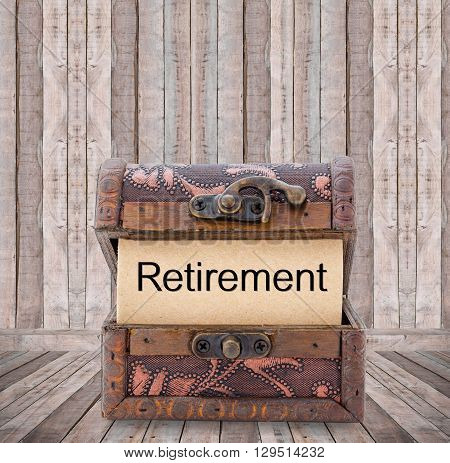 Retirement word on paper in treasure chest on wooden room.