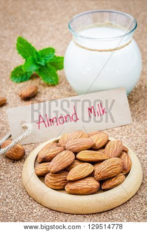 Almond and almond milk on wooden table.