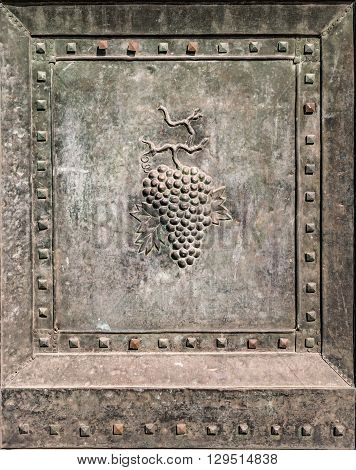 Bunch of grapes embossed in an ancient bronze door.