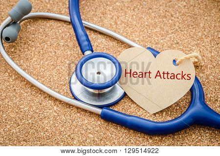 Medical conceptual. HEART ATTACKS word on label tag heart shape and stethoscope on wooden background.