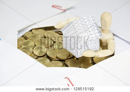 Wooden Dummy Holding House Surrounded By Gold Coins And Paperwork