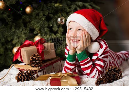 portrait of beautiful smiling boy lying by christmas tree at home enjoying winter time at home waiting for a miracle to happen