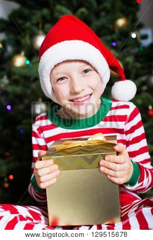 portrait of beautiful smiling boy holding christmas present by the tree at home enjoying winter time at home