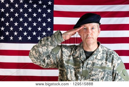 Veteran soldier facing forward saluting with USA flag in background.