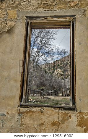 Looking at a stock pen from a wood framed window in a dilapidated building in a ghost town