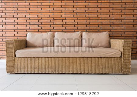Rattan Sofa With Grey Cushions And Red Brick Wall