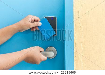 Hand Holding Blue Hotel Keycard In Front Of Electric Door