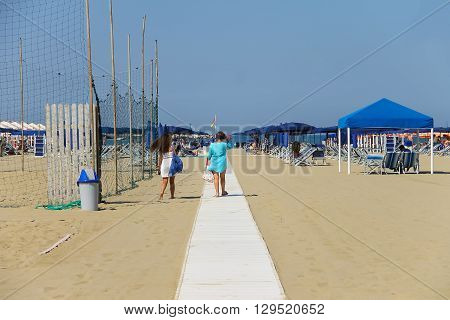 Viareggio Italy - June 28 2015: Two young women walking on the beach. Viareggio is the famous resort on the coast of the Ligurian Sea. Province Lucca Tuscany region of Italy