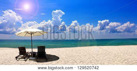 Beach chair and umbrella near the beach with blue sky
