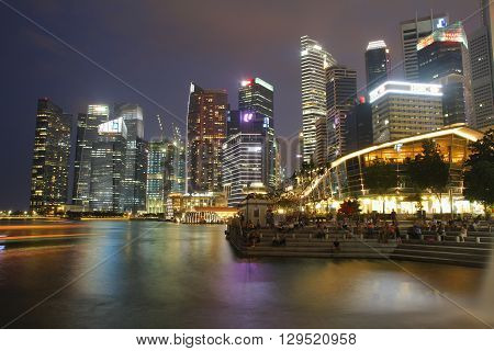 SINGAPORE - APRIL 10 2016: Financial district skyscrapers and the Jubilee Bridge at Merlion Park. A newly created pedestrian bridge at Marina Bay