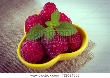 Vintage photo Fresh raspberries and leaf of lemon balm in bowl on wooden table concept of healthy food and dessert