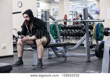 Strong man, Bodybuilder sits on a weight bench in a gym, he takes a break