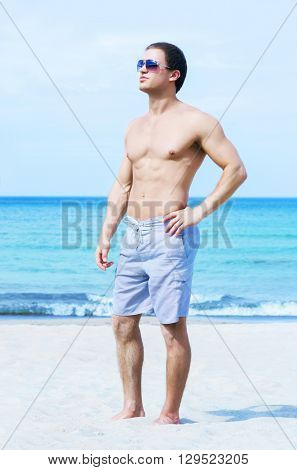 Young, fit and handsome man with athletic and muscled body walking on a summer beach
