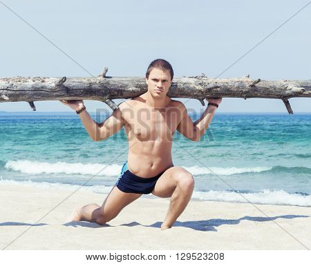 Young, handsome and athletic man training on a beach at summer
