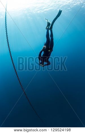 The underwater scenes. Scuba diver swims under water with chain
