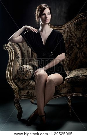 Sensual young woman sitting on baroque sofa in elegant black dress, looking away.