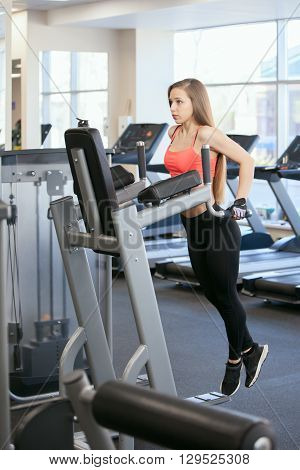 Beautiful young girl engaged in fitness in the gym. Brunette performs exercises on the simulator.