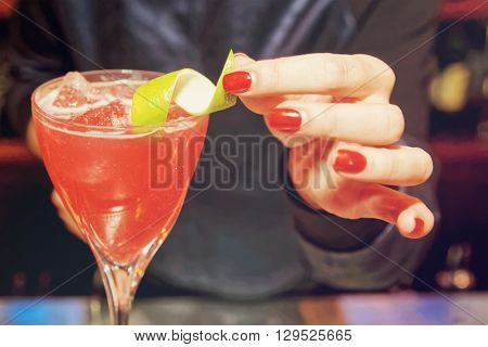 Female bartender is decorating a cocktail with lime zest, toned image