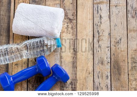 Blue dumbbellstowel and bottle water on wooden table. Fitness concept