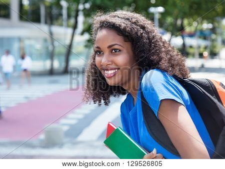 Happy latin female student with curly hair outdoor in the city