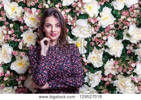 Woman On Flower Wall Smiling Ar Camera