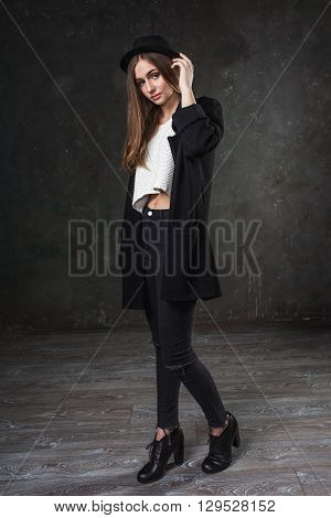 Joyful pretty girl wearing black costume and black classic hat. Hipster style.