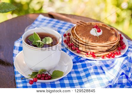 Russian style pancakes with redcurrants and mint tea outdoors