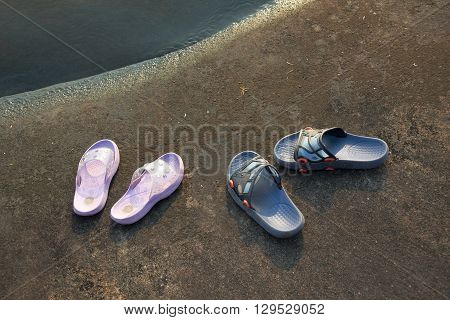 Man's and woman's flip flops at the beach